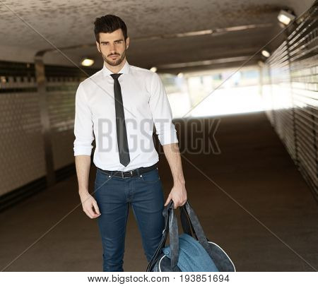 Handsome young man standing in underpass, looking at camera, holding sports bag.