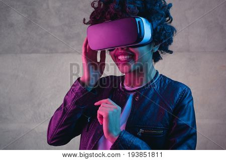 Pretty smiling girl touching her head wearing the virtual reality helmet.