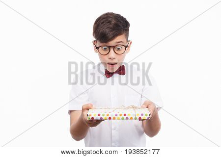 Small boy in glasses holding giftbox and looking at it with surprise.