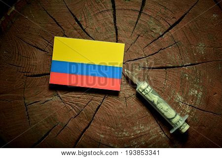 Colombian Flag On A Stump With Syringe Injecting Money In Flag