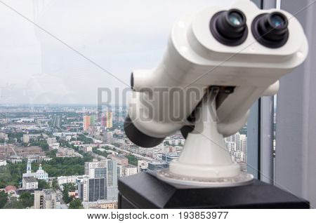 Binoculars on the observation desk on the roof of high building