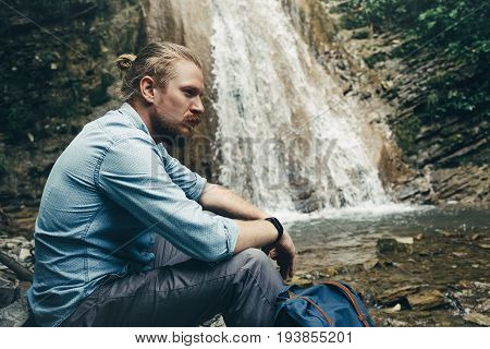 Tourist Traveler With Backpack Sitting On Rocks Near Waterfall Trek Hiking Destination Experience Lifestyle Concept