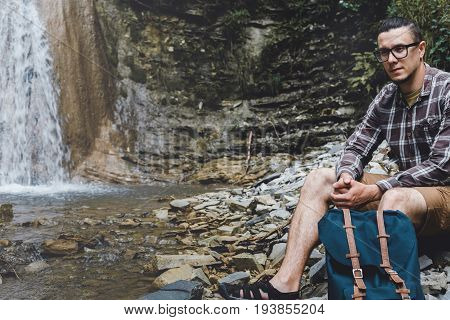 Male Backpacker Sitting On The Rocks Near Waterfall Hiking Destination Experience Lifestyle Concept