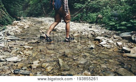 Unrecognizable Tourist With Backpack Crosses Wild River Into ford. Trek Hiking Destination Experience Lifestyle Concept