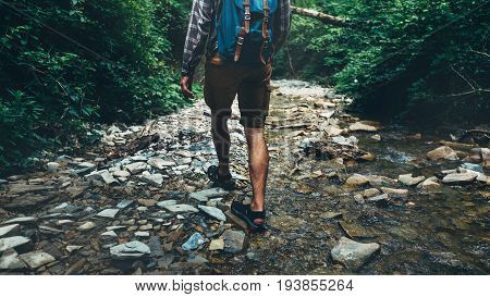 Unrecognizable Traveler Man With Backpack Walks Along Mouth Of Mountain River In Forest Rear View. Trek Hiking Destination Experience Lifestyle Concept