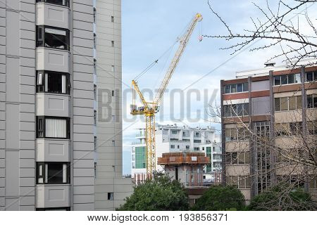 Construction crane in Auckland CBD with apartment buildings and office blocks New Zealand NZ