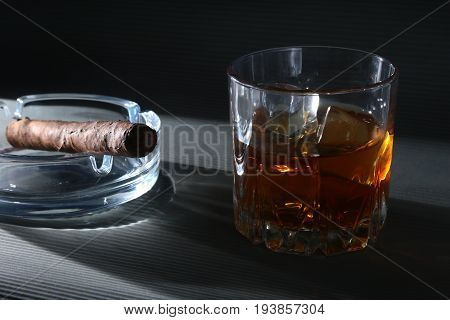 Glass of whiskey or bourbon with ice and cigar on black stone table. Selective focus