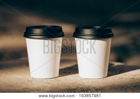 Two cups of coffee to go in white paper cups in sunlight. Morning coffee for couple in love. Place for text.