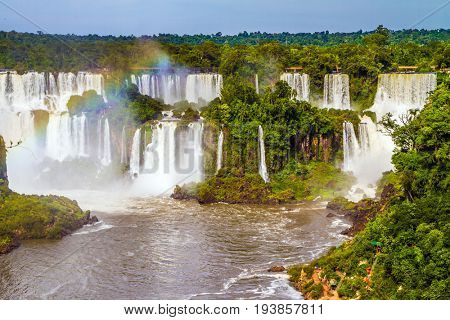 Several waterfalls from 275 Iguazu Falls. Boiling water creates a watery dust and a rainbow. The concept of exotic and extreme tourism