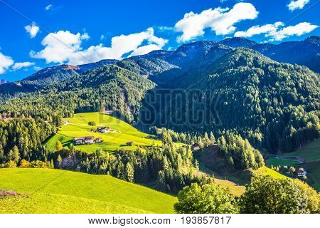 Rural pastoral in the Dolomites. Warm autumn day. Charming chalet on a green grassy slope of the mountain. The concept of ecological t