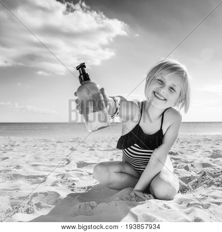 Smiling Healthy Child In Swimwear On Seacoast Showing Lotion
