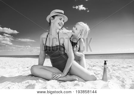 Smiling Young Mother And Child On Seashore Applying Spf