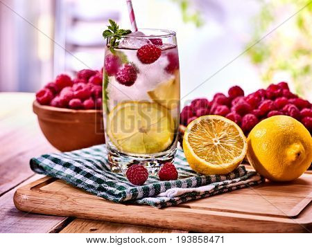 Cold non alcoholic cocktails with lemon slice and raspberries with mint leaf. Lemonade ice cubes. Nonalcoholic beverage on wooden board. Table setting rural style with cooling summer drink homemade.