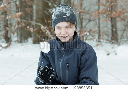 Boy Playing With Snowball Outside