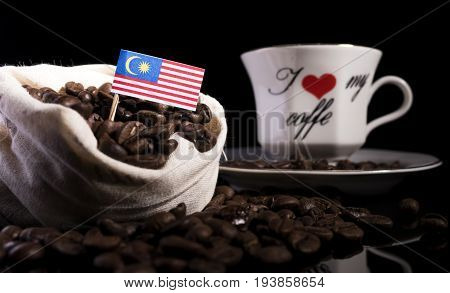 Malaysian Flag In A Bag With Coffee Beans Isolated On Black Background