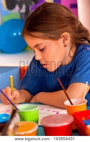 Small students painting in art school class. Child drawing by paints on table. Close up of little girl in kindergarten. Drawing education develops creative abilities of children. Incorrect seat at