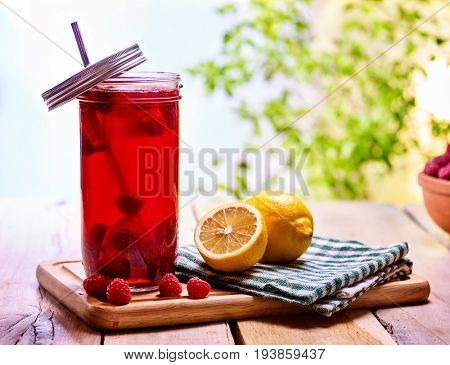 Cold non alcoholic cocktail with lemon half and raspberries. Nonalcoholic beverage in cocktail glass with cocktail straw on wooden board. Table setting rural style with drinks in village.