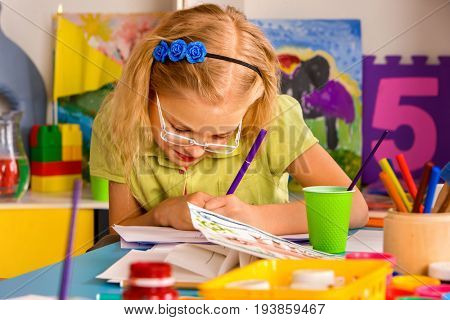 Small students painting in art school class. Child drawing by paints on table. Portrait of little girl in kindergarten. Schoolchild Incorrect seat at table.
