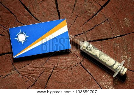 Marshall Islands Flag On A Stump With Syringe Injecting Money In Flag