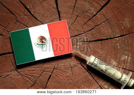 Mexican Flag On A Stump With Syringe Injecting Money In Flag
