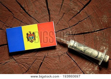 Moldovan Flag On A Stump With Syringe Injecting Money In Flag