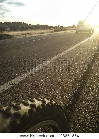 Car overtaking a mountain bike on local road at sunset. Closeup