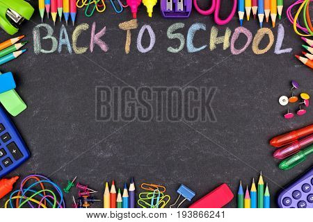School Supplies Frame With Back To School Written In Colorful Chalk With Against A Chalkboard Backgr