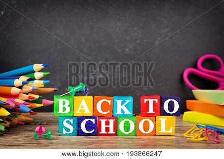 Colorful Back To School Wooden Blocks With School Supplies And Chalkboard In Background