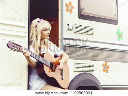 Young hippie girl playing guitar outdoors at summer. Holiday, journey, vacation concept.