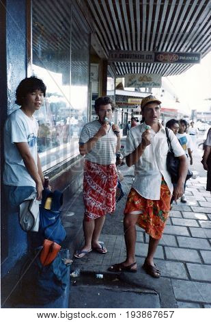 APIA / SAMOA - CIRCA 1990: American tourists don Polynesian garb and eat ice cream on a sidewalk in Apia, the capital city of Samoa.