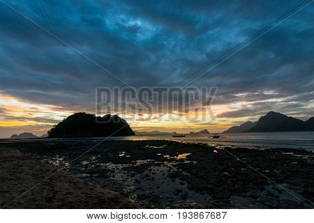 EL NIDO, PALAWAN, PHILIPPINES - MARCH 29, 2017: Sun going down behind the clouds of Las Cabanas Beach.