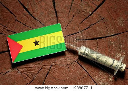 Sao Tome And Principe Flag On A Stump With Syringe Injecting Money In Flag