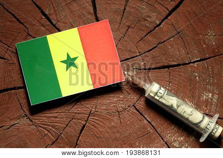 Senegal Flag On A Stump With Syringe Injecting Money In Flag