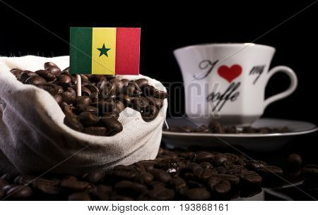 Senegal Flag In A Bag With Coffee Beans Isolated On Black Background