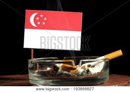 Singaporean Flag With Burning Cigarette In Ashtray Isolated On Black Background