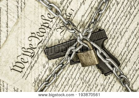 A locked handgun symbolizing gun rights while framed against the United States constitution.