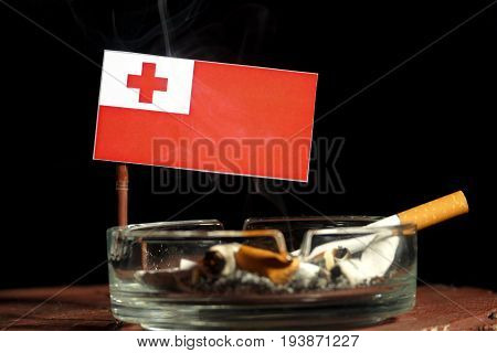 Tongan Flag With Burning Cigarette In Ashtray Isolated On Black Background