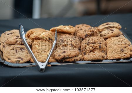 Variety tray of chocolate chip, raisin, and oatmeal cookies with tongs.