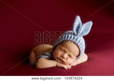 Little newborn baby girl 7 days, sleeps. newborn baby curled up sleeping on a blanket. Eight day old smiling newborn baby girl.