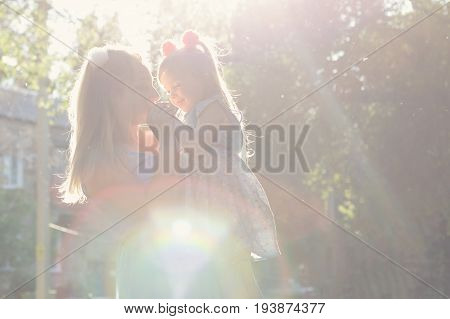 Family values. Mother and daughter. Mother hold the child in her arms. Same dresses and hairstyles. Backlight of the setting sun. Portrait in the park. Family look