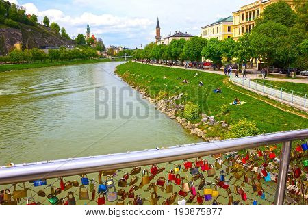 Salzburg, Austria - May 01, 2017: The people resting near bridge fence covered with locks in Salzburg. Salzburger Land, Austria on May 01, 2017