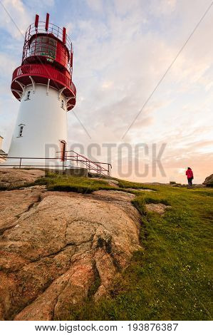 Tourist woman and historic red white lighthouse on the edge of rocky sea coast South Norway Lindesnes Fyr beacon