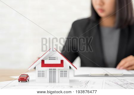 House model on blueprint paper at the table with blurred businesswoman in background - real estate and property agent concept