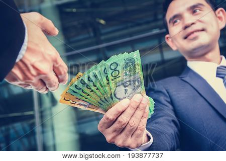 Businessmen passing money Australia dollar (AUD) banknotes