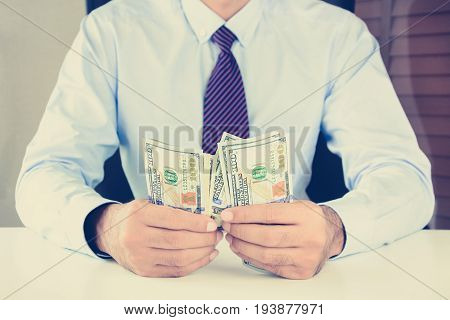 Businessman counting moneyUS dollar (USD) bills on the table