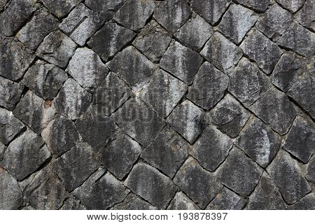 Ancient Japanese stone wall, gray, sooty stones arranged in diamond pattern, diagonally, for use as background or wall paper.