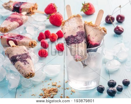 Homemade popsicle and cherry, blueberry, strawberry, raspberry on blue wooden background. Healthy summer breakfast. Popsicles from yogurt and banana with berries, granola and chia seeds