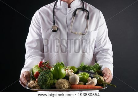 Doctor nutritionist holding a tray of fresh organic vegetables. Health care and medical concept. Healthy eating and Detoxification concept.