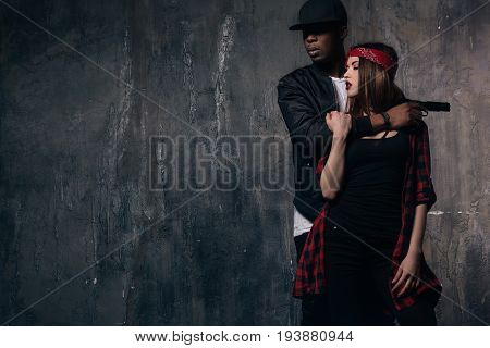 Hostage inlove in gangster with gun. Victim hugs with black criminal mafia person on dark background