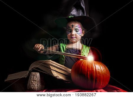 Little cute girl costumed as a witch reads the Book of Spells. Selective focus